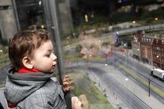 Garçon regardant la ville de jouet Photographie stock