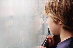 Garçon regardant par la fenêtre Photos libres de droits