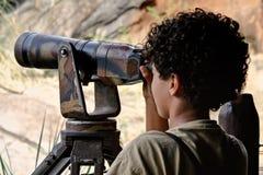 Garçon regardant par le télescope Photo libre de droits