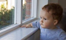 Garçon regardant par un hublot Photographie stock