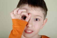 Garçon regardant par une main Images stock