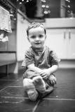 Garçon reposé sur le plancher de cuisine Photos stock