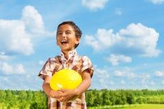 Garçon riant avec la boule photo stock