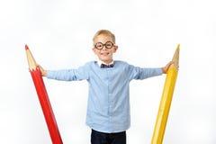 Garçon riant en verres et bowtie posant avec les crayons énormes Concept éducatif D'isolement au-dessus du blanc images stock