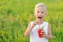 Garçon riant heureux tenant un verre de pastèque fraîche rouge de jus Jeunes adultes Style de vie sain photo stock