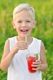Garçon riant heureux tenant un verre de pastèque fraîche rouge de jus Jeunes adultes Style de vie sain photos stock