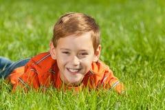 Garçon riant sur l'herbe image stock