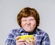 Garçon roux couvert de taches de rousseur comique avec le téléphone portable Photos stock