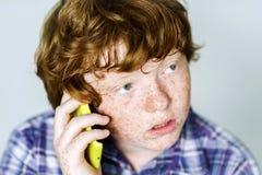 Garçon roux couvert de taches de rousseur comique avec le téléphone portable Photo libre de droits