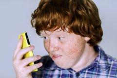 Garçon roux couvert de taches de rousseur comique avec le téléphone portable Image stock