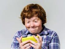 Garçon roux couvert de taches de rousseur comique avec le téléphone portable Photos libres de droits