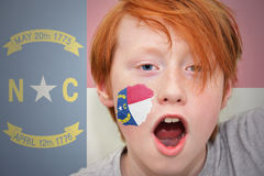 Garçon roux de fan avec le drapeau d'état de la Caroline du Nord peint sur son visage Photo stock