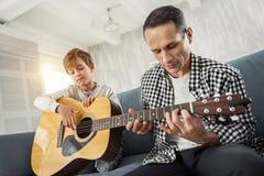 Garçon sérieux apprenant comment jouer la guitare Image stock
