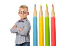 Garçon sérieux en verres et bowtie posant près des crayons colorés énormes Concept éducatif D'isolement au-dessus du blanc photos libres de droits
