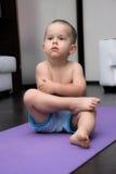 Garçon sérieux s'asseyant sur un tapis de yoga Photographie stock