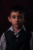 Garçon sérieux sur le fond brun Photos libres de droits