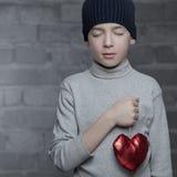 Garçon sérieux tenant le coeur, studio Photos libres de droits