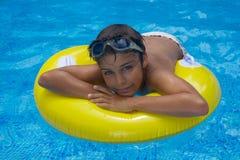 Garçon s'étendant sur l'anneau en caoutchouc dans la piscine Image libre de droits