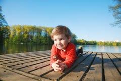 Garçon s'étendant sur le dock au lac photo stock