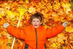 Garçon s'étendant sur les feuilles d'automne avec le râteau Image stock
