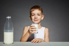 Garçon s'asseyant avec le verre de lait Photographie stock