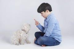 Garçon s'asseyant avec son chien Photo libre de droits