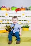 Garçon s'asseyant avec un bouquet des fleurs dans un costume de denim Photo stock