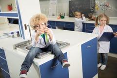 Garçon s'asseyant dans l'évier dans le laboratoire de science et tenant des tubes à essai avec des réactifs images libres de droits