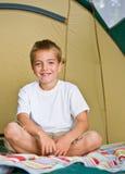 Garçon s'asseyant dans la tente photographie stock libre de droits