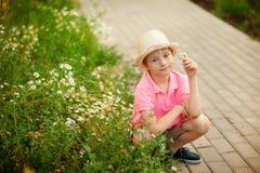 Garçon s'asseyant dans le temps de fleurs au printemps Photo libre de droits