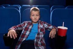Garçon s'asseyant dans le théâtre de cinéma, film de observation attentivement image libre de droits