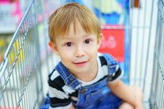 Garçon s'asseyant dans un chariot d'épicerie Photo libre de droits