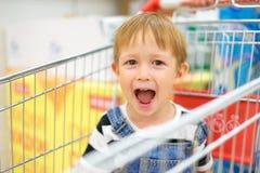 Garçon s'asseyant dans un chariot et rire d'épicerie Image libre de droits