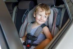 Garçon s'asseyant dans une voiture dans la chaise de sécurité images libres de droits