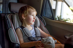 Garçon s'asseyant dans une voiture dans la chaise de sécurité Photographie stock