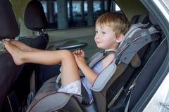 Garçon s'asseyant dans une voiture dans la chaise de sécurité Images stock