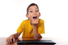 Garçon s'asseyant devant l'ordinateur Image stock