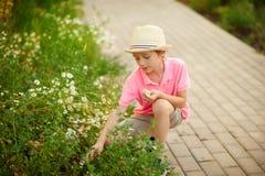 Garçon s'asseyant en fleurs au printemps Images stock