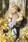 Garçon s'asseyant sous l'arbre images stock