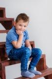 Garçon s'asseyant sur des escaliers Photographie stock libre de droits