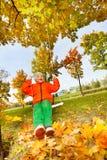 Garçon s'asseyant sur des oscillations, souriant pendant le jour d'automne photos stock