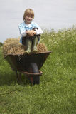 Garçon s'asseyant sur Hay In Wheelbarrow At Field Photographie stock libre de droits