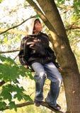 Garçon s'asseyant sur l'arbre Images libres de droits