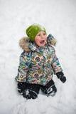 Garçon s'asseyant sur la neige photos stock