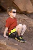 Garçon s'asseyant sur la roche photos stock