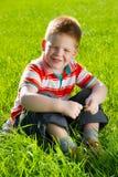 Garçon s'asseyant sur la zone de l'herbe Photos stock