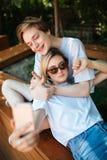 Garçon s'asseyant sur le banc en parc et montrant heureusement le pouce tandis que fille avec les cheveux blonds se penchant sur  image libre de droits