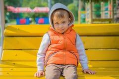 Garçon s'asseyant sur le banc jaune Photos libres de droits