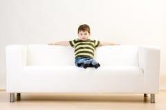 Garçon s'asseyant sur le divan Image libre de droits