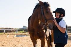 Garçon s'asseyant sur le dos de cheval image stock
